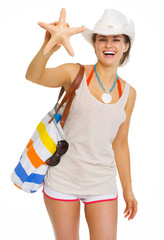 Smiling young woman with beach bag showing starfish