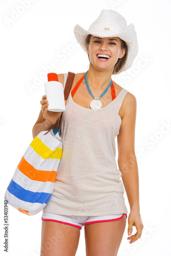 Happy young woman with beach bag showing sun screen creme
