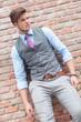 casual man poses at a brick wall