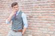 casual man smoking by brick wall