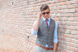 casual man leans on wall and adjust sunglasses