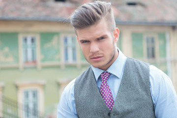 casual man with tie and vest looks at you