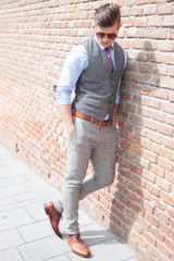 casual man leans on wall and looks down