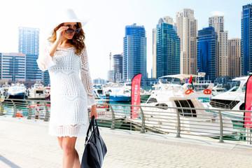 frau mit weißem kleid am yachthafen