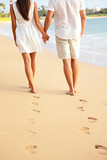 Couple holding hands walking on beach on vacation