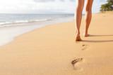 Fototapety Beach travel - woman walking on sand beach closeup