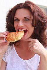 Lecker croissant mit einer hübschen Frau beim essen