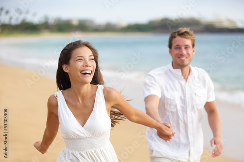 Beach couple running having fun laughing together