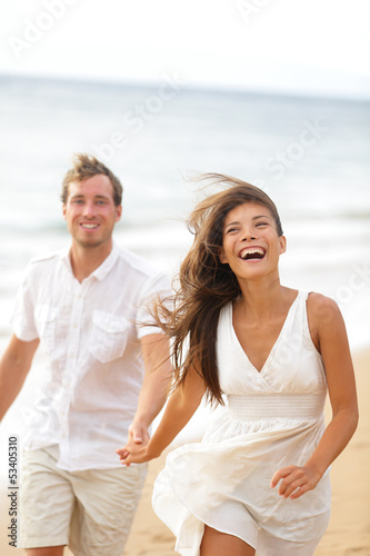 Beach fun - couple laughing and running together