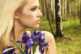 Beautiful blond woman with blue flowers in forest. summer