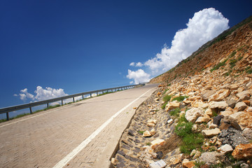 Road going up to hill and clouds on blue sky in summer day