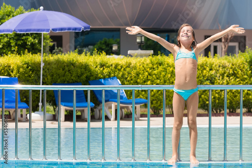 Girl sunbathing on edge of pool raised his hands up