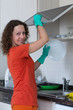 Cute housewife washing dishes in rubber gloves