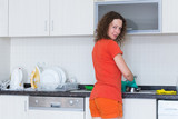 Smiling housewife washing dishes in rubber gloves
