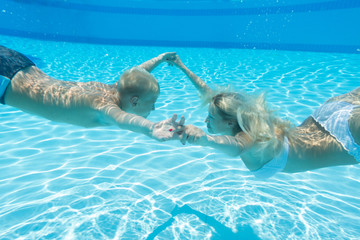 Mother and son swim underwater holding hands in pool