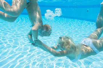 Mother and son swimming under water in the pool
