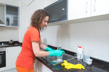 Cute housewife washing dishes with a sponge in rubber gloves