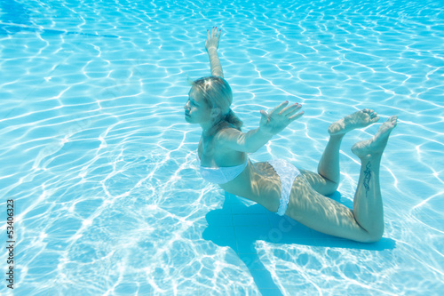 Underwater girl with closed eyes and tattoo on leg
