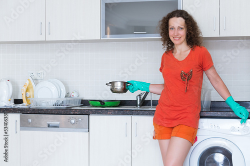 Smiling housewife holds pot in his hand in rubber gloves