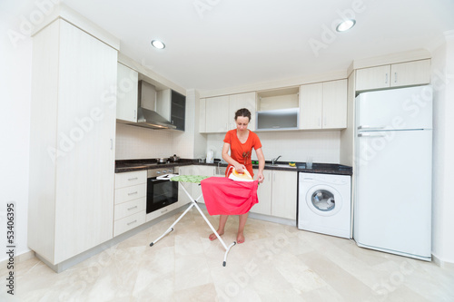 Housewife ironing laundry in middle of the kitchen