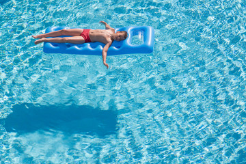 boy floats on an inflatable mattress in pool face up