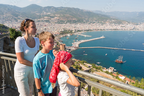 Family of three looking at beautiful view of sea from hill