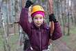 Little girl climber is ready to the passage the ropes course