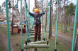 Boy climber walks on the rope bridge on ropes course