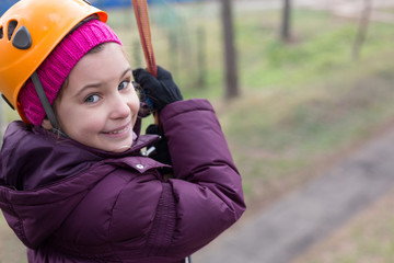 Little girl with climbing equipment hanging on a rope