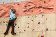 Young climber rises to the climbing wall.