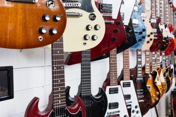 Electric guitars hanging on wall in the shop