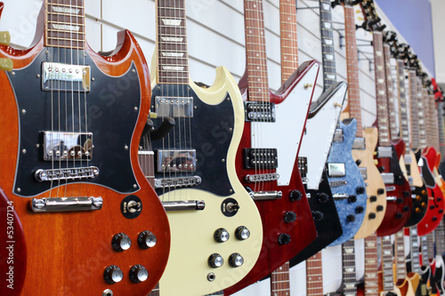 Many electric guitars hanging on wall in the shop © Pavel Losevsky