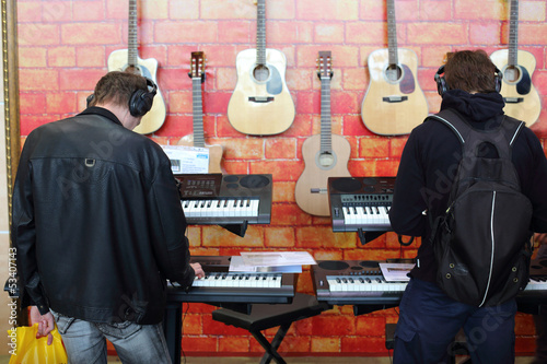 People playing the keyboards with headphones
