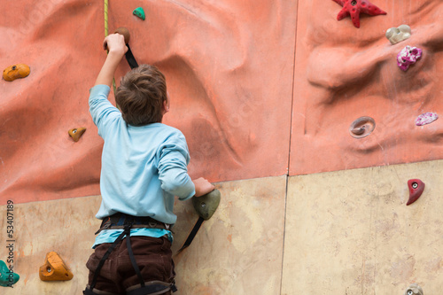 Young guy with climbed equipment rises to the climbing wall.