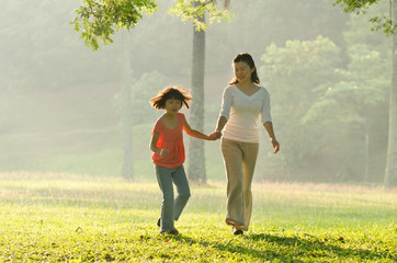 Asian mother holding her daughter's hand walking in the park