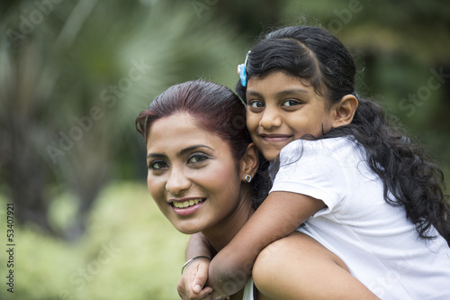 Happy Indian mum and her child playing outdoors