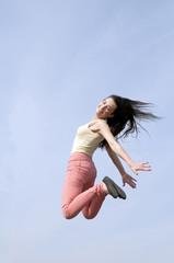 lachende Frau macht Freudensprung