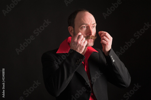 Low key portrait of man adjusting moustache