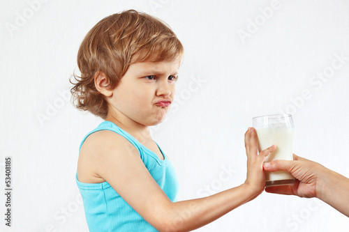 Little cute blonde boy refuses drink a fresh milk