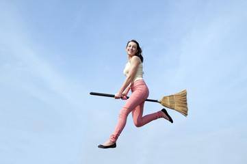 junge Frau fliegt mit Besen