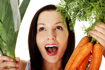 Happy woman in apron holding fresh leek and carrot