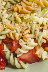 Colorful salad with pasta and variety of vegetables.