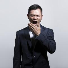 Chinese business man yawning.