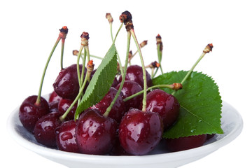 Fresh cherry berries with green leaf isolated