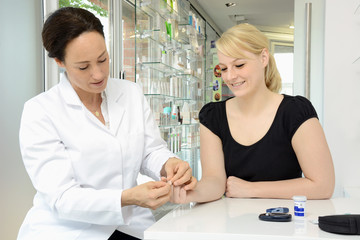 Apothekerin klebt Pflaster nach Blutzuckerbestimmung auf