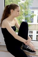 Teenager sitzt traurig auf Fensterbank