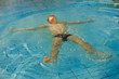 Young man floating in swimming pool