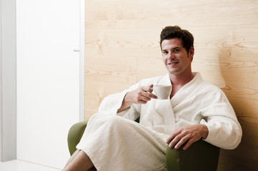 Young man in robe relaxing in health spa