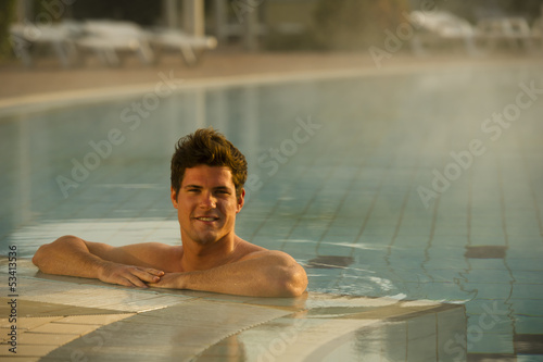Young man in health club swimming pool