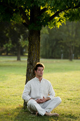 Young man meditating under a tree